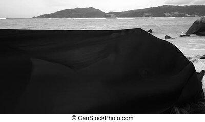 Sensual woman at the beach covered sheer fabric
