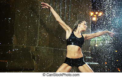 Sensual woman dancing in a fountain