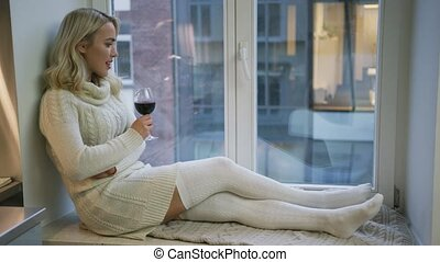 Sensual woman drinking wine on window sill