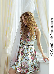 Sensual woman in a dress with curly hair