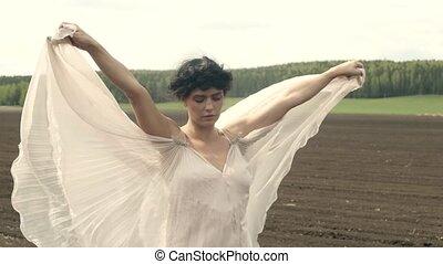 Sensual woman in dress on field
