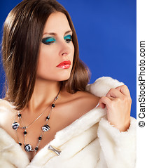 Sensual woman in fur on blue background with jewellery