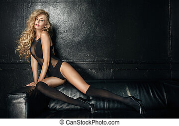 Sensual woman in seductive black lingerie sitting on a couch