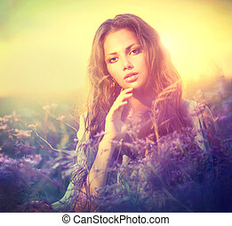 Sensual Woman Lying on a Meadow with Violet Flowers