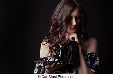 Sensual woman photographer with an old camera
