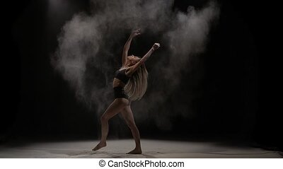 Sensual woman throwing dust particles in air. Slow motion