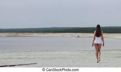 Sensual woman walking along beach on tiptoe showing swimwear...
