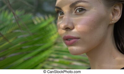 Sensual woman wearing black swimwear on a beautiful summer day between palm trees
