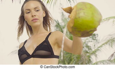 Sensual woman wearing black swimwear on a beautiful summer day between palm trees