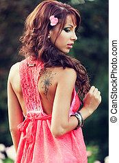 Sensual woman with tattoo on her back