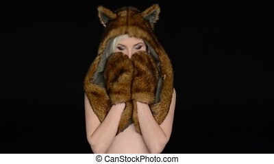 Sensual woman without underwear wearing fur earflaps and...