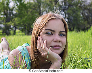 sensual young blonde lying on the grass outdoors