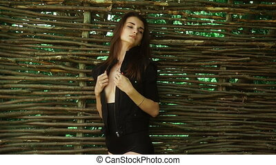 sensual young brunette lady in provocative clothes stands at the fence and looking aside