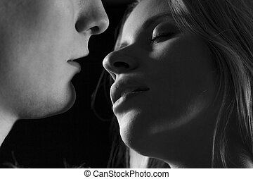 Black and white close-up of sensual young couple kissing each other
