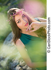 Sensual young lady in wreath wearing green dress