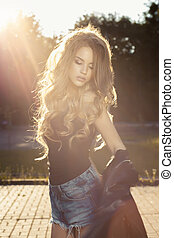 Sensual young lady with lush wave hair posing in rays of sun