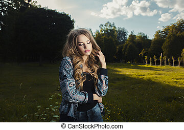 Sensual young model with long curly hair posing in the park