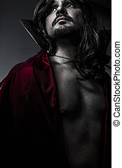 Sensual Young Vampire with black coat and long hair, nude
