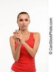 Sensual young woman holding perfume bottle. Beautiful woman...