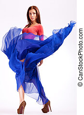 sensual young woman in a blue fluttering dress