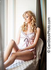 sensual young woman sitting at sill
