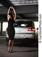 Sensual young woman stading and posing on car parking