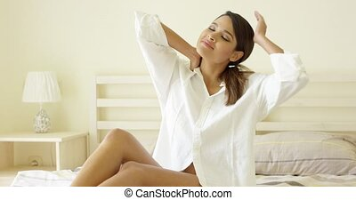 Sensual young woman stretching on her bed