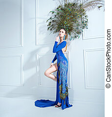 Sensual young woman wearing a giant hat made of peacock