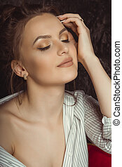 Sensual young woman with natural makeup in striped shirt