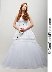 Sensuality. Romantic Fiancee in White Long Dress with Bouquet of Flowers