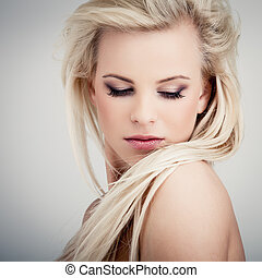 Sensuality - Young blond lady with a beautiful hair on gray...