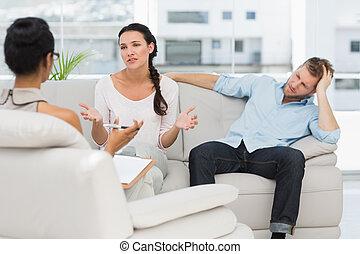 sentado, enojado, sofá, hablar, terapeuta, pareja