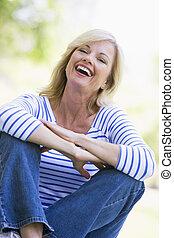 sentado, mujer, reír, aire libre