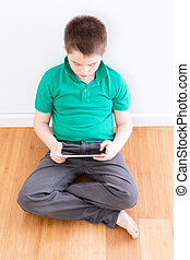 sentado, niño joven, tenencia, tableta, reclinado, pared