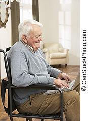 sentando, cadeira rodas, incapacitado, usando, sênior, laptop, homem