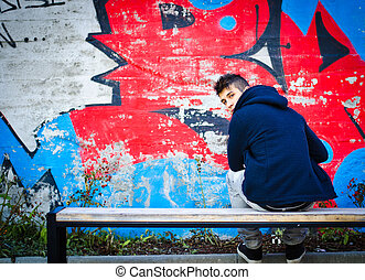 sentando, jovem, banco, graffiti, hoodie, frente, homem