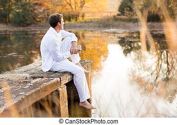 sentando, jovem, pôr do sol, homem, desfrutando, cais, vista