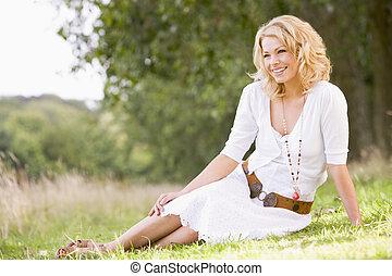 sentando, mulher sorridente, ao ar livre