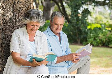 sentando, par, árvore, junto, LIVROS, maduras, tronco, leitura