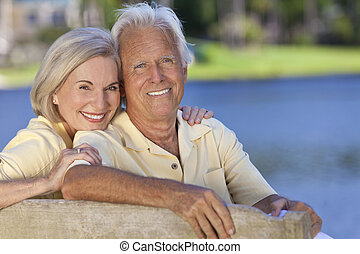 sentando, par, banco parque, abraçar, sorrindo, sênior, feliz