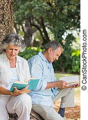 sentando, par, velho, árvore, junto, LIVROS, tronco, leitura, Feliz
