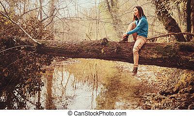 sentando, sobre, tronco árvore, menina, rio