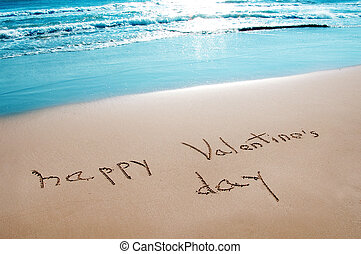 "sentence ""happy valentines day"" written on the sand of a beach"