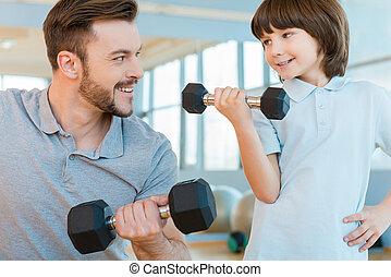 sentiment, fier, de, sien, son., heureux, père fils, exercisme, à, dumbbells, et, sourire, quoique, debout, dans, club santé, ensemble