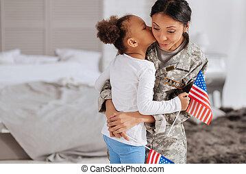 Sentimental young girl kissing her beloved mother -...