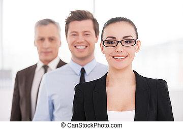 sentimento, confiante, aproximadamente, dela, team., bonito, mulher jovem, em, formalwear, e, óculos, olhando câmera, e, sorrindo, enquanto, dela, colegas, ficar, uma fileira, atrás de, dela