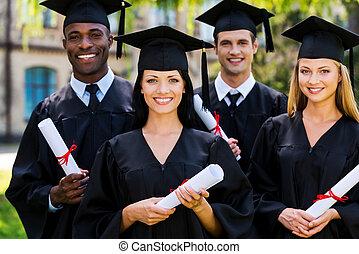 sentimiento, confiado, en, su, future., cuatro, colegio, graduados, en, trajes de ceremonia de entrega de diplomas, posición, cerca de, uno al otro, y, sonriente
