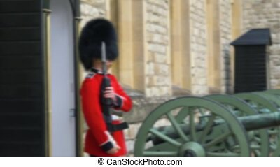 Blurred video footage. Traditional march of the British guard at the combat post. British Guard Soldier of patrols near Tower of London of duty of Queen of England. Queen's Guard - Tower of London.