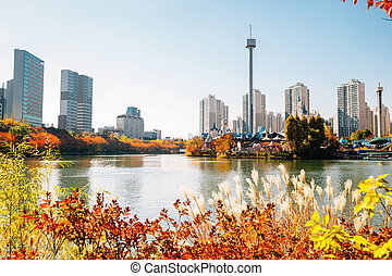 Seokchon lake and modern apartment buildings with autumn maple in Seoul, Korea