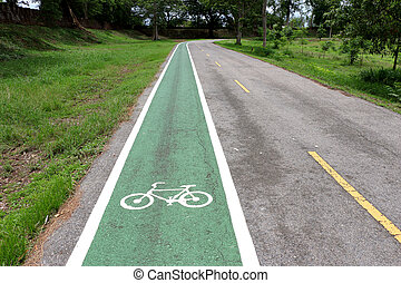 Separate bicycle lane on asphalt in the park. White bike symbol